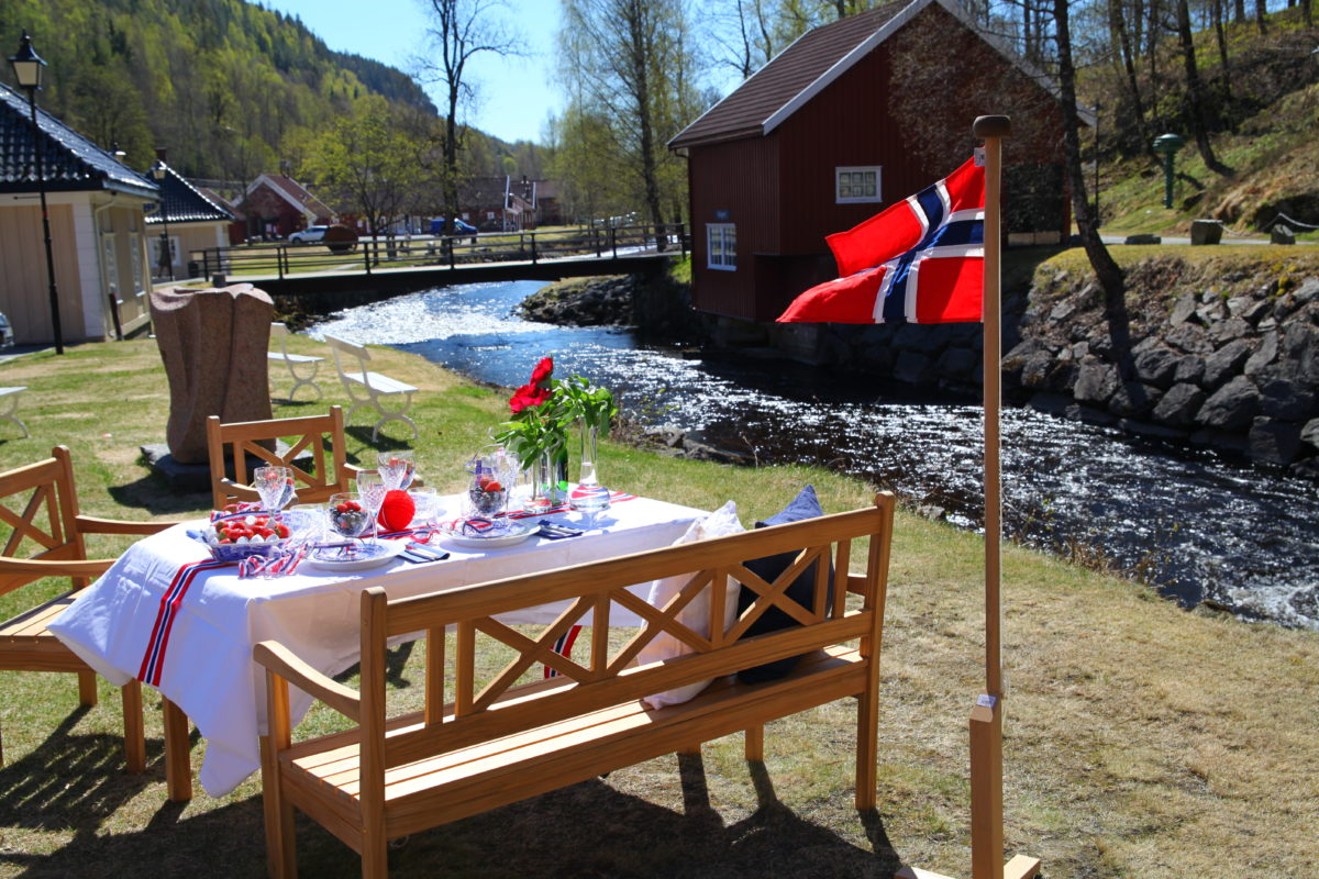 Dekket 17.mai bord med norsk flagg på gresset utenfor Verket Interiør på Bærums Verk i strålende sol.