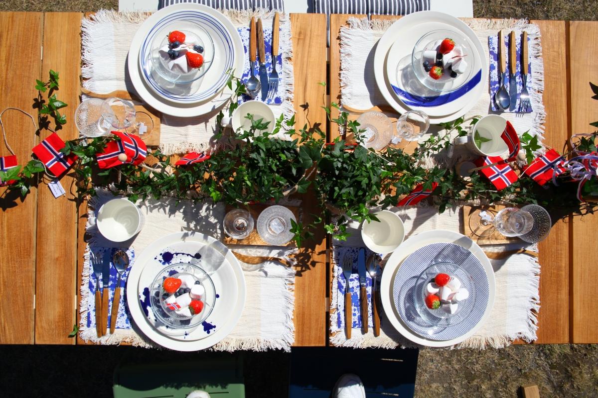 Dekket 17.mai bord med norsk flagg på gresset utenfor Verket Interiør på Bærums Verk i strålende sol. Møbler fra Cane-line