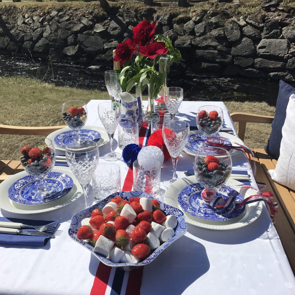 Dekket 17.mai bord med norsk flagg på gresset utenfor Verket Interiør på Bærums Verk i strålende sol. Møbler i teak fra Skagerak Denmark.