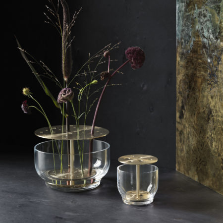 Miljøbilde av Ikebana vasen fra serien Objects by Fritz Hansen. EN stor og en liten i glass med messinglokk. Blomster i den store.