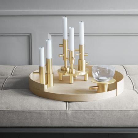 Miljøbilde av lysestaken Objects Candleholder fra Fritz Hansen i messing stående på et brett på et bord.