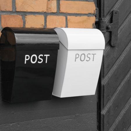 Miljøbilde av Postkasse mini fra Bruka. En sort og en hvit med sølv tekst på.