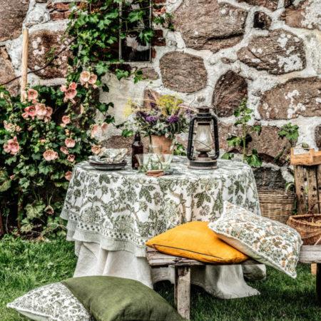 Floral linduk i fargen olive fra Chamois. Miljøbilde av dekket bord.