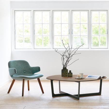 Miljøbilde av Insula sofabord fra Erik Jørgensen i mørkebrunt tre og Eyes Lounge stol i grønt..