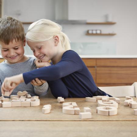 Miljøbilde av barn som leder med Alfabetklosser i tre fra Kay Bojesen.