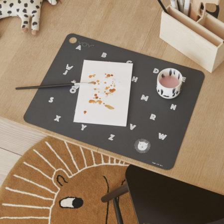 Miljøbilde av skrivebord ståendes på gulvteppe løve