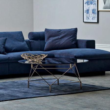 Miljøbilde av en blå sofa og sofabordet Spider med glassplate fra Eilersen