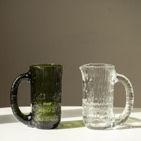 Vannfall karaffel fra Nedre Foss i klart glass og en i grønt glass på et bord