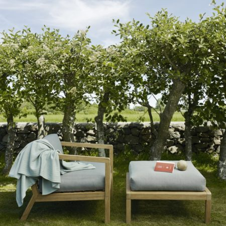 Miljøbilde av hagemøbler fra Skagerak Design. Puff Virkelyst i teak med grå puter.