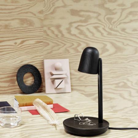 Miljøbilde av Focus trelampe i sort fra Muuto stående på et skrivebord.